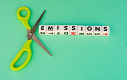 Cut emissions. Text ' emissions ' inscribed on small white cubes in black upper case text with a pair of scissors included to indicated cutting, green background royalty free stock photography