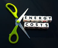 Cut energy costs. Text ' energy costs ' inscribed in black uppercase letters  on small white cubes with scissors to indicate reduction, dark background Royalty Free Stock Image