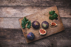 Cut Figs on chopping board and wooden table Royalty Free Stock Images