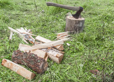 Cut firewood and old axe on green grass. Environmental concept Stock Photo