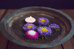 Cut flowers and candle in vintage bowl Royalty Free Stock Photography