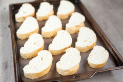 Cut french loaf bread on baking tray Stock Image