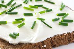 Cut fresh chives on thickly spread cream cheese on dark health bread Stock Photography