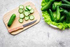 Cut fresh cucumbers on cutting board. Grey background top view copyspace. Cut fresh cucumbers on cutting board. Grey background top view Stock Image