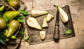 Cut fresh pears on old cutting Board, with a basket full of pears. Royalty Free Stock Photo