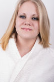Cut fresh young woman in a bathrobe in a spa. With a white background behind her Stock Photo
