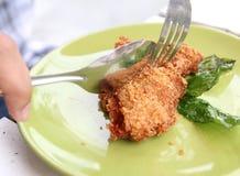 Cut fried shrimp cake. Closeup image of a man holding spoon and fork cut fried shrimp cake Stock Photo