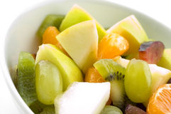 Cut fruit close up. A close up of a fresh fruit salad. Contains grapes, orange, plum, melon, kiwi and apple royalty free stock photo