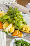 Cut fruit composition served on the table. Fruit setting with grapes, orange, pineapple, apple Stock Photos