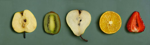 Cut fruit - orange, pear, strawberry, kiwi, apple on kitchen board Royalty Free Stock Images