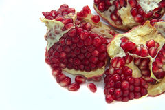 Cut the fruit pomegranate. Seeds, large berries, skin color from orange-yellow to brownish-red, on white background, , photograph up close Stock Image
