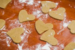 Cut gingerbread in a heart shape on a wooden table, poured with wheat flour stock photography