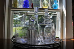 Cut glass decanters in window Royalty Free Stock Photography
