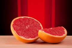 Cut grapefruit on a board with abstract red background Royalty Free Stock Image
