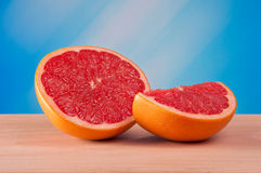 Cut grapefruit on a board with a light blue background Stock Image