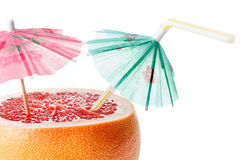 Cut grapefruit cocktail with umbrella, isolated on white Royalty Free Stock Photos