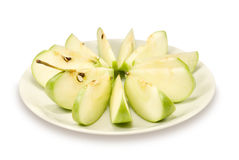 The cut green apple lays on a plate Royalty Free Stock Photos
