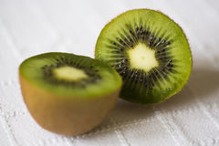 Cut green fruit kiwi with black seeds and white core Stock Images