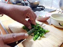 Cut green onion with a kitchen knife on a wooden cutting board stock photo