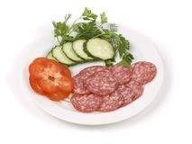 Cut green-stuffs and pieces of sausage. On a white dish Royalty Free Stock Photos