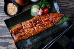 Cut grilled Japanese eel. Cut Japanese eel grilled or Unagi ibaraki set on plate in Japanese style with studio lighting royalty free stock photo