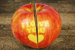 Cut in half apple with an inscription I love you on wood Royalty Free Stock Image