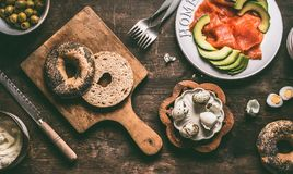 Cut in half bagel bun on wooden gutting board with bread knife and sandwich ingredients: salmon, avocado, hummus and quail eggs. Top view royalty free stock photo