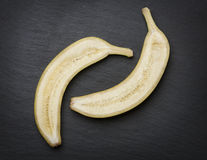 Cut in half banana on dark stone slab. Stock Images