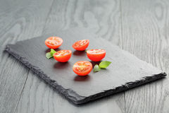 Cut in half cherry tomatoes on slate board Stock Photos