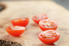 Cut in half cherry tomatoes on wood table Stock Images
