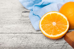 A cut in half exotic orange. Bright oranges on a wooden background. Antioxidant fruits for healthy drinks. Copy space. Royalty Free Stock Images