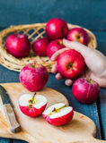Cut in half fresh red apples on a wooden board, fruits Royalty Free Stock Photos