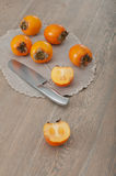 Cut in half kaki fruit. Cut in half persimmon fruit with whole kaki on the background royalty free stock photography