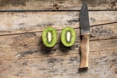 Cut in Half Kiwi with Knife lying on Textured Wooden Table. Top View Royalty Free Stock Images