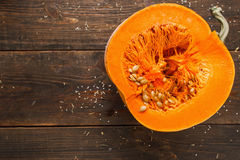 Cut half of pumpkin on wood free space flat lay. Cut half of orange pumpkin on wood free space flat lay. Top view on rustic wooden table with cutaway fresh Royalty Free Stock Image