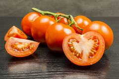Cut in half a red tomato on a wooden table. Royalty Free Stock Photos