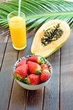 Cut in Half Ripe Papaya Fresh Strawberries Tropical Juice in Tall Glass with Straw Palm Leaf on Plank Wood Table in Cafe Royalty Free Stock Photo