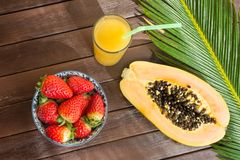 Cut in Half Ripe Papaya Fresh Strawberries Tropical Juice in Tall Glass with Straw. Palm Leaf on Plank Wood Table in Cafe. Vacations Summer Travel Concept stock photos