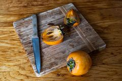 Cut in half and whole persimmon on a wooden background stock image