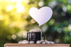Cut a heart paper on a coffee mug on a wooden board and a Bokeh tree backdrop. Cut a heart paper on a coffee mug on a wooden board and a Bokeh tree backdrop Stock Image