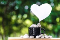 Cut a heart paper on a coffee mug on a wooden board and a Bokeh tree backdrop. Cut a heart paper on a coffee mug on a wooden board and a Bokeh tree backdrop Royalty Free Stock Images