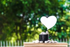 Cut a heart paper on a coffee mug on a wooden board and a Bokeh tree backdrop. Royalty Free Stock Images
