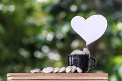 Cut a heart paper on a coffee mug on a wooden board and a Bokeh tree backdrop. Stock Photography