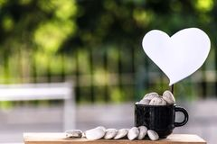 Cut a heart paper on a coffee mug on a wooden board and a Bokeh tree backdrop. Stock Images