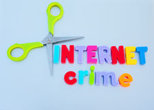 Cut internet crime. Text ' internet crime' in colorful letters with scissors placed beside the text to spell cutting, or reducing,  blue gray background Royalty Free Stock Photography