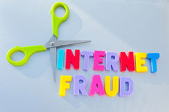 Cut internet fraud. Text 'internet fraud' in colorful uppercase letters with pair of scissors next to text, silvery gray background Royalty Free Stock Photos