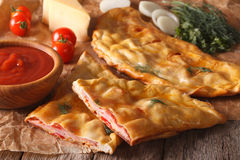 Cut Italian pizza calzone with ham closeup and ingredients. hori Royalty Free Stock Images