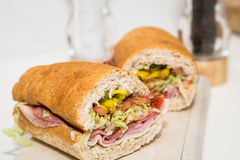 Cut Italian Sub on Wood Cutting Board Royalty Free Stock Photo