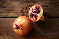 Cut juicy ripe pomegranate on a wooden table Royalty Free Stock Image