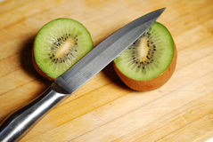 Cut by a kiwi on chopping board Stock Images